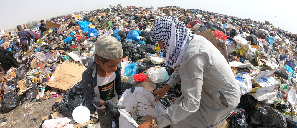 Iraqi people collect recyclable garbage at a dump, amidst concerns about the spread of the coronavirus disease (COVID-19), in Basra, Iraq May 6, 2020. Picture taken May 6, 2020. REUTERS/Mohammed Aty - RC29MG9DERFZ