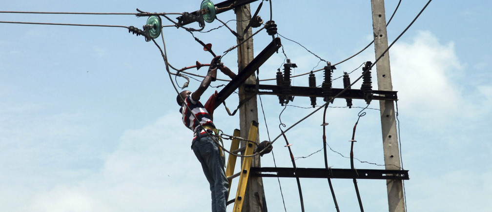 A power official works on an electric pole along a street in Nigeria's commercial capital Lagos October 3, 2012.REUTERS/Akintunde Akinleye(NIGERIA - Tags: ENERGY SOCIETY) - RTR38QYK