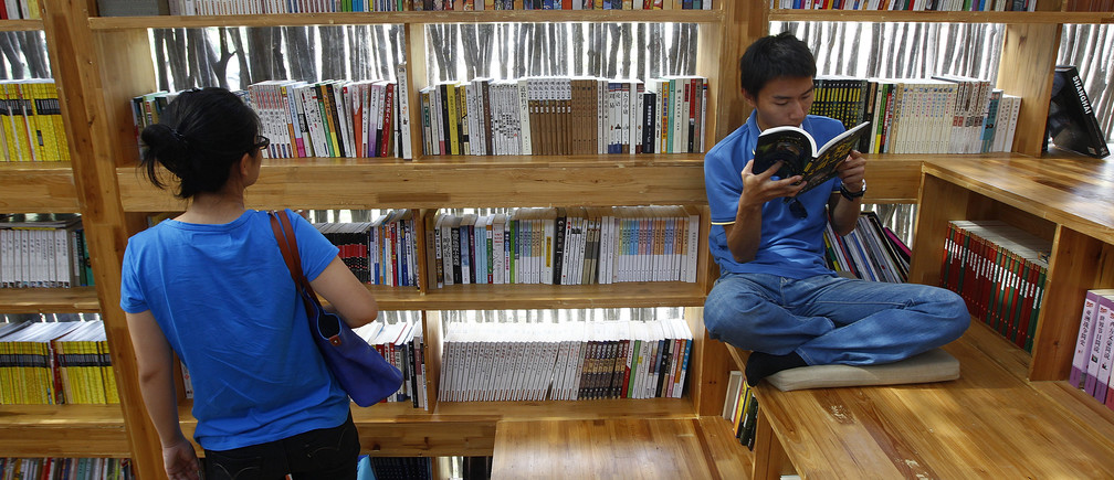 Visitors read books at the Liyuan Library at Jiaojiehe village of Huairou district, in Beijing, September 8, 2012.The 175-square-metre library, designed by Professor Li Xiaodong from the School of Architecture of Tsinghua University, took seven months to build and costs more than one million yuan ($157,660). A total of 45,000 firewood sticks were used to cover the glass wall of the building. The library has no electricity supply and closes at 4.30pm when the light fades. The library opens its door to public for free every weekend, local media reported. REUTERS/Barry Huang (CHINA - Tags: SOCIETY) - GM1E8981SUI01