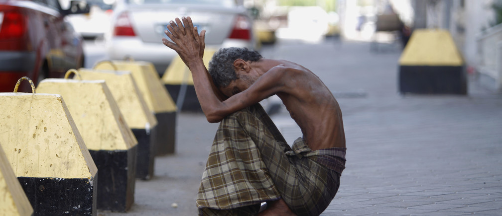 A homeless man sits on the side of a street in the port city of Aden October 8, 2012.