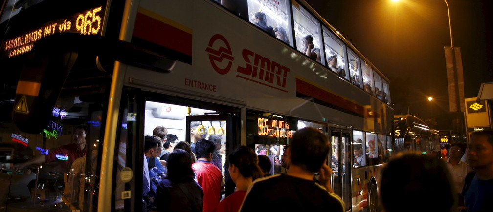 Affected commuters board buses at a North-South line train station after train services were disrupted during evening rush hour in Singapore, July 7, 2015. According to train operator SMRT, train services along the North-South and East-West lines came to a halt due to a traction power fault. REUTERS/Edgar Su  - GF10000151462