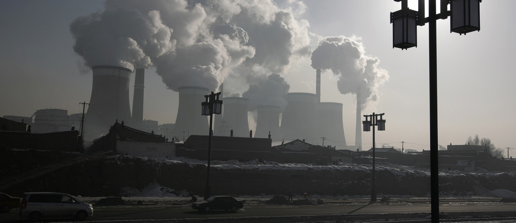 A man walks near a coal-fired power plant on the outskirts of Datong, Shanxi province, November 20, 2009. China will raise power prices for non-residential users by around 5.4 percent from Friday, the first rise since July 2008, to compensate grid firms that lost out because of a government cap on prices. REUTERS/Jason Lee (CHINA ENERGY ENVIRONMENT BUSINESS) - RTXQXVR