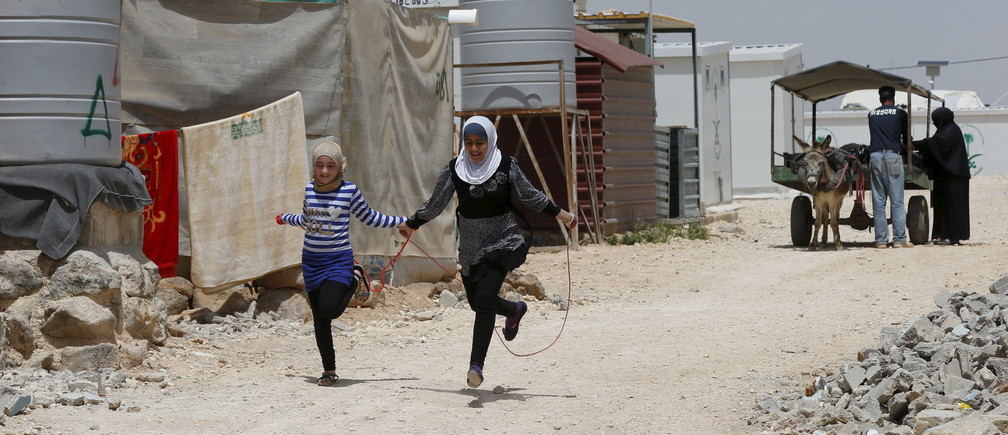 Syrian refugee Omayma al Hushan (R), 14, who launched an initiative against child marriage among Syrian refugees, plays with her friend outside their residence in Al Zaatari refugee camp in the Jordanian city of Mafraq, near the border with Syria, April 21, 2016. REUTERS/Muhammad Hamed - RTX2BYKC