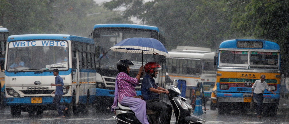 People ride a scooter through a road as it rains in Kolkata, India, July 2, 2019. REUTERS/Rupak De Chowdhuri - RC1408B94890