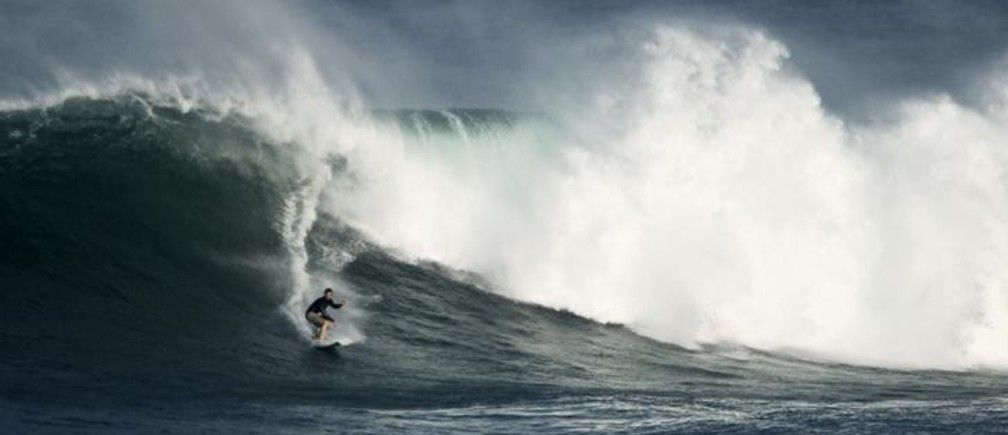 A surfer rides a large wave during high surf advisory conditions at Waimea Bay on the Northshore of O'ahu, Hawaii January 4, 2012. TREUTERS/Anthony Bolante (UNITED STATES - Tags: SPORT ENVIRONMENT)