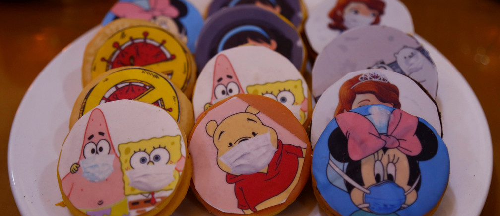 Biscuits depicting cartoons wearing protective masks are pictured at a cake shop during the outbreak of the coronavirus disease (COVID-19), in the holy city of Najaf, Iraq April 24, 2020. Picture taken April 24, 2020. REUTERS/Alaa al-Marjani - RC2CCG9QECTQ