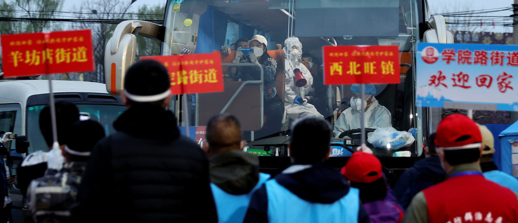 People returning from Hubei province, the epicentre of China's coronavirus disease (COVID-19) outbreak, arrive at an assembly point as workers of their communities wait to pick them up, in Beijing, China March 25, 2020. Picture taken March 25, 2020. cnsphoto via REUTERS. ATTENTION EDITORS - THIS IMAGE WAS PROVIDED BY A THIRD PARTY. CHINA OUT. - RC2GRF9LCDGI