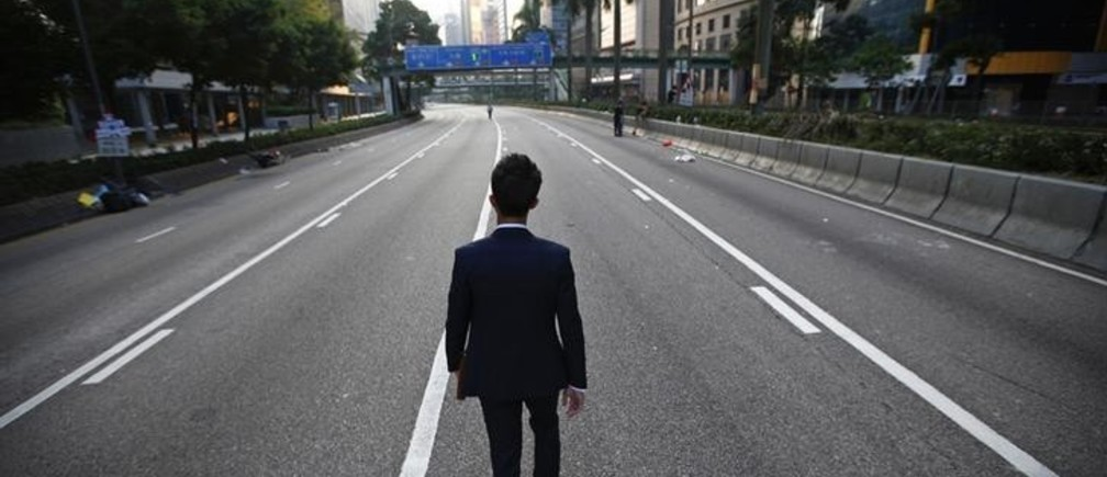 A man walks along an empty street near the central financial district in Hong Kong September 30, 2014. Tens of thousands of pro-democracy protesters extended a blockade of Hong Kong streets on Tuesday, stockpiling supplies and erecting makeshift barricades ahead of what some fear may be a push by police to clear the roads before Chinese National Day.   REUTERS/Carlos Barria (CHINA - Tags: POLITICS CIVIL UNREST)