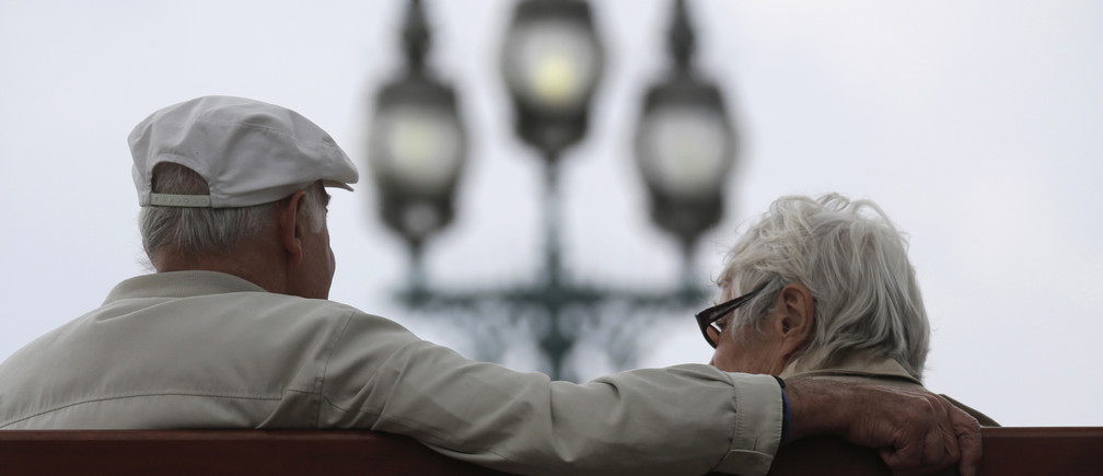 A retired couple sits on a bench in Enghien-les-Bains, north of Paris, August 26, 2013. France's government, which has been meeting with labour union heads about retirement issues, neared a deal with trade unions on Monday to overhaul the pension system via a slight lengthening of working lives, union chiefs said, as Europe's number two economy sought to bring a spiralling deficit under control. REUTERS/Christian Hartmann (FRANCE - Tags: POLITICS BUSINESS EMPLOYMENT) - RTX12X57