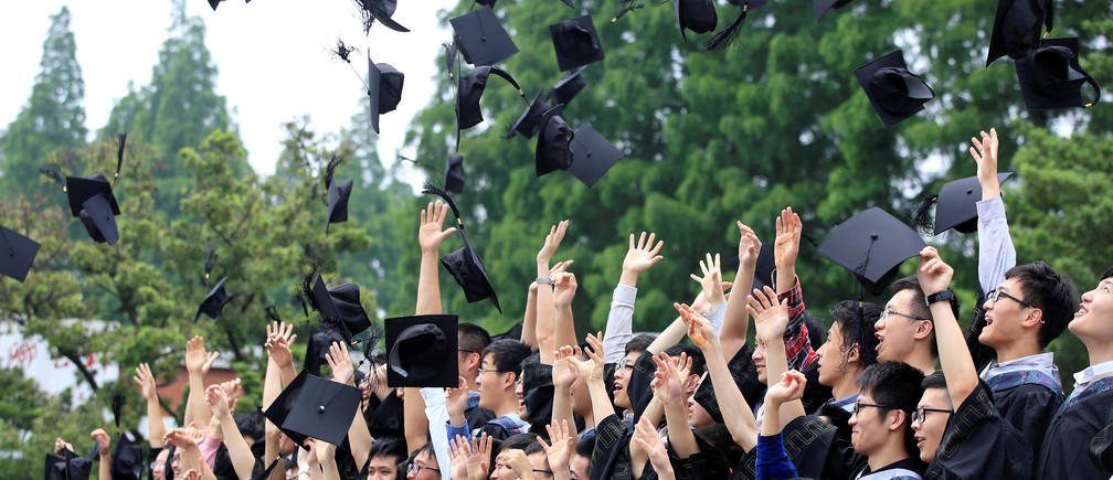 Graduates throw their mortar boards as they pose for pictures at Fudan University in Shanghai