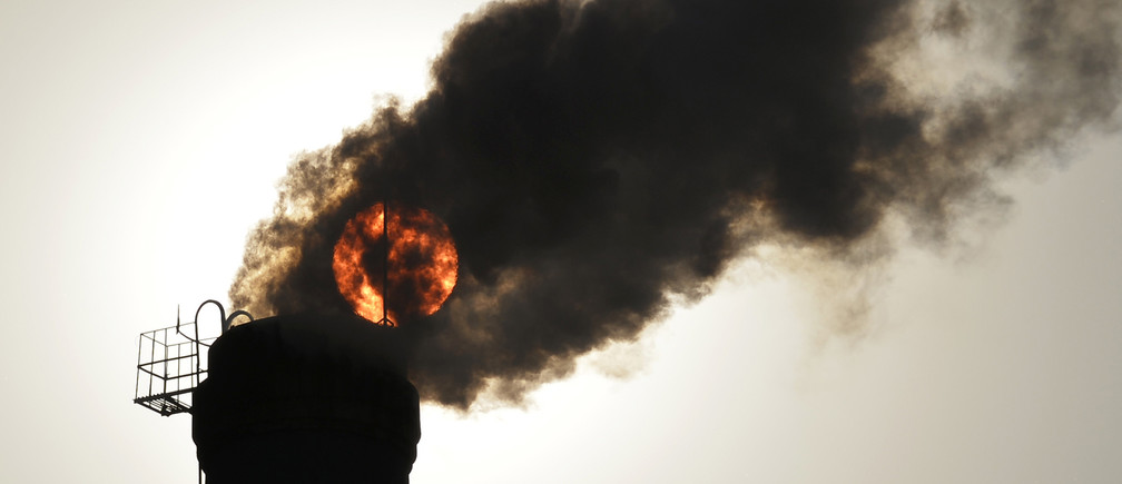 The sun is seen behind smoke billowing from a chimney of a heating plant in Taiyuan, Shanxi province December 9, 2013. A coal-dependent manufacturing base has made China the world's biggest contributor to climate change, while high and rising local air-pollution levels have sparked widespread complains from the public nationwide. REUTERS/Stringer (CHINA - Tags: ENVIRONMENT POLITICS ENERGY) CHINA OUT. NO COMMERCIAL OR EDITORIAL SALES IN CHINA - GM1E9C91FTL01