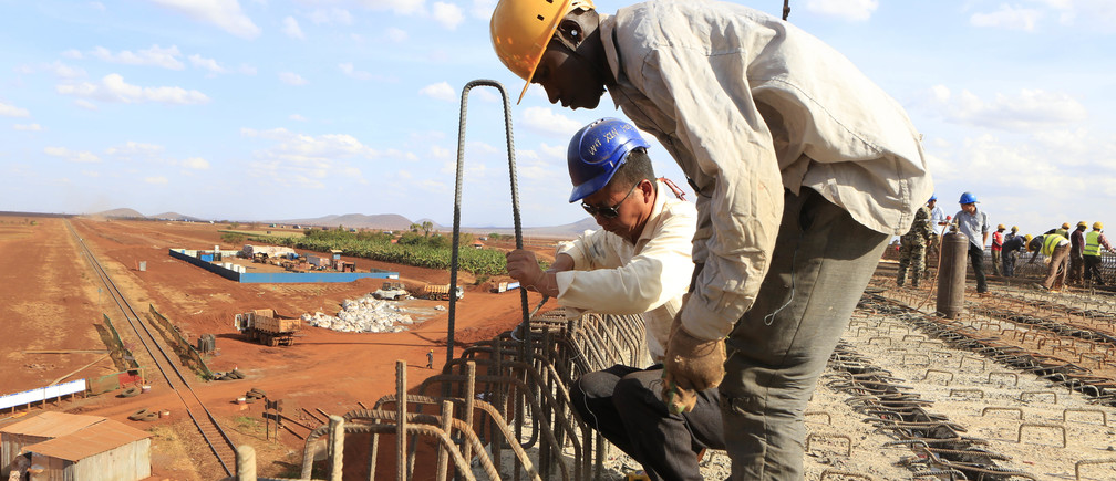 A Chinese engineer and a local construction worker work on a section of the Mombasa-Nairobi standard gauge railway (SGR) in Emali, Kenya October 10, 2015. The China Road and Bridge Corporation (CRBC) tasked with the construction work at a cost of 3.8 billion U.S. dollars is due for completion in mid-2017. REUTERS/Noor Khamis  - D1AERZDORFAA