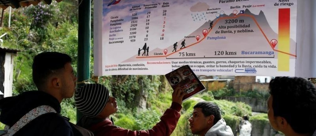 Undocumented Venezuelan migrants look at a banner with information about the route from Cucuta to Bucaramanga at a makeshift shelter for Venezuelan migrants in Pamplona, Colombia August 25, 2018. The majority of the migrants have never left Venezuela and sometimes struggled to understand the magnitude of the journey ahead.