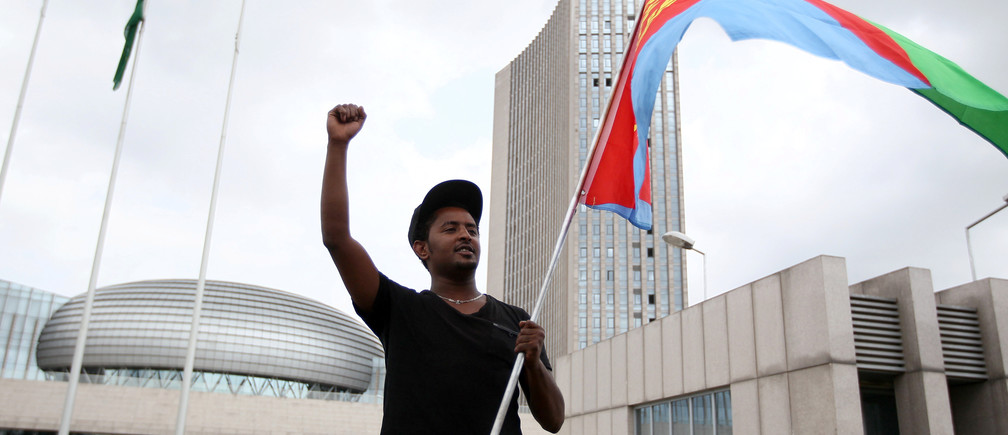 An Eritrean refugee holds his national flag as he participates in a demonstration in support of a U.N. human rights report accusing Eritrean leaders of crimes against humanity in front of the Africa Union headquarters in Ethiopia's capital Addis Ababa, June 23, 2016. REUTERS/Tiksa Negeri - RTX2HRYZ