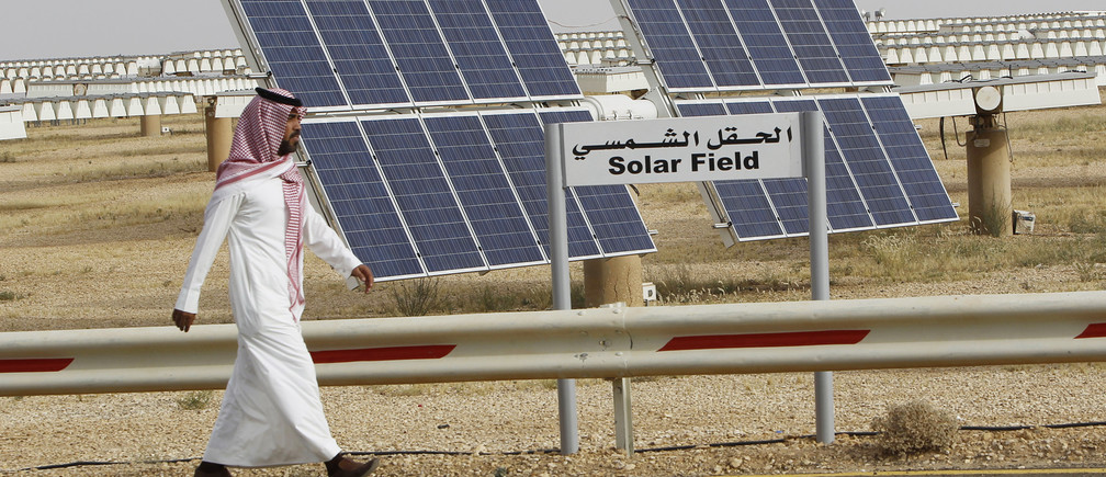 A Saudi man walks on a street past a field of solar panels at the King Abdulaziz city of Sciences and Technology, Al-Oyeynah Research Station, May 21, 2012. Saudi Arabia, the world's top oil exporter, may finally be getting serious about overcoming the technical and financial hurdles for tapping its other main resource: sunshine. Saudi Arabia wants to generate much more solar power as it lacks coal or enough natural gas output to meet rapidly rising power demand. Doing so would allow it to slash the volume of oil it burns in power plants bankrolled by billions of dollars worth of saved oil earnings. Picture taken May 21, 2012. To match story SAUDI-SOLAR/  REUTERS/Fahad Shadeed   (SAUDI ARABIA - Tags: ENERGY BUSINESS) - RTR32IDZ