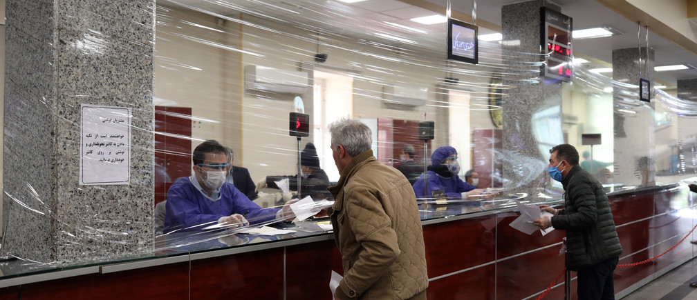 A plastic cover is seen between the Bank employees and the clients, as they wear protective face masks, following the outbreak of coronavirus, in Tehran, Iran March 17, 2020. WANA (West Asia News Agency)/Ali Khara via Coronavirus china virus health healthcare who world health organization disease deaths pandemic epidemic worries concerns Health virus contagious contagion viruses diseases disease lab laboratory doctor health dr nurse medical medicine drugs vaccines vaccinations inoculations technology testing test medicinal biotechnology biotech biology chemistry physics microscope research influenza flu cold common cold bug risk symptomes respiratory china iran italy europe asia america south america north washing hands wash hands coughs sneezes spread spreading precaution precautions health warning covid 19 cov SARS 2019ncov wuhan sarscow wuhanpneumonia  pneumonia outbreak patients unhealthy fatality mortality elderly old elder age serious death deathly deadly