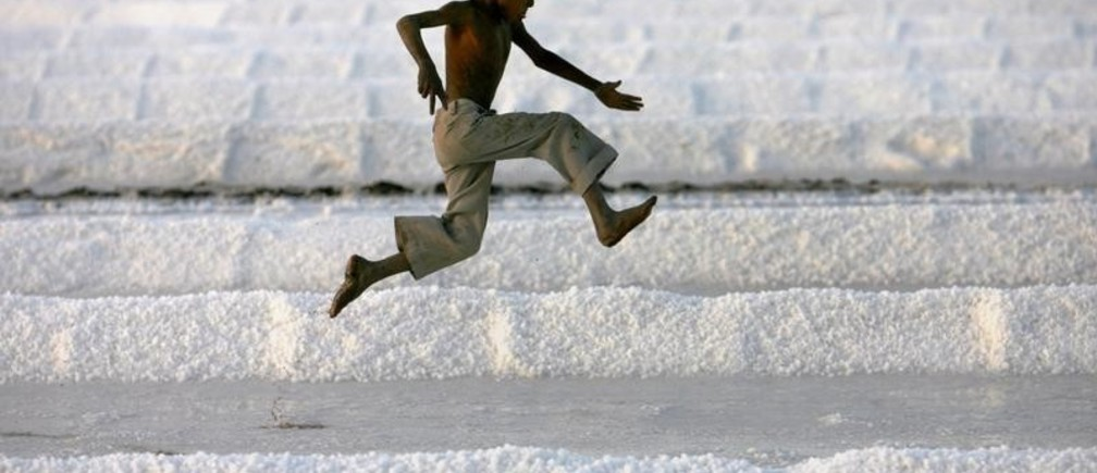 A worker's son plays in a salt pan near Bhavnagar, in the western Indian state of Gujarat March 5, 2009. REUTERS/Arko Datta (INDIA) - GM1E5360FML01