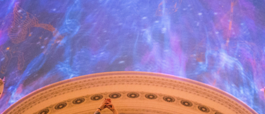 A woman takes photographs of a light show on the ceiling of Grand Central Terminal which organizers said was honoring the work of female scientists and engineers in Manhattan, New York, U.S., September 19, 2017. REUTERS/Adrees Latif - RC16911FC040