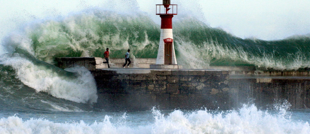 Giant waves crash over onlookers washing them off the sea wall of Cape Town's Kalk Bay harbour, August 27, 2005. The two men were later rescued as storms created waves of an estimated nine metres.