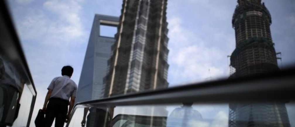 A man rides an escalator near Shanghai Tower (R, under construction), Jin Mao Tower (C) and the Shanghai World Financial Center (L) at the Pudong financial district in Shanghai July 4, 2013.