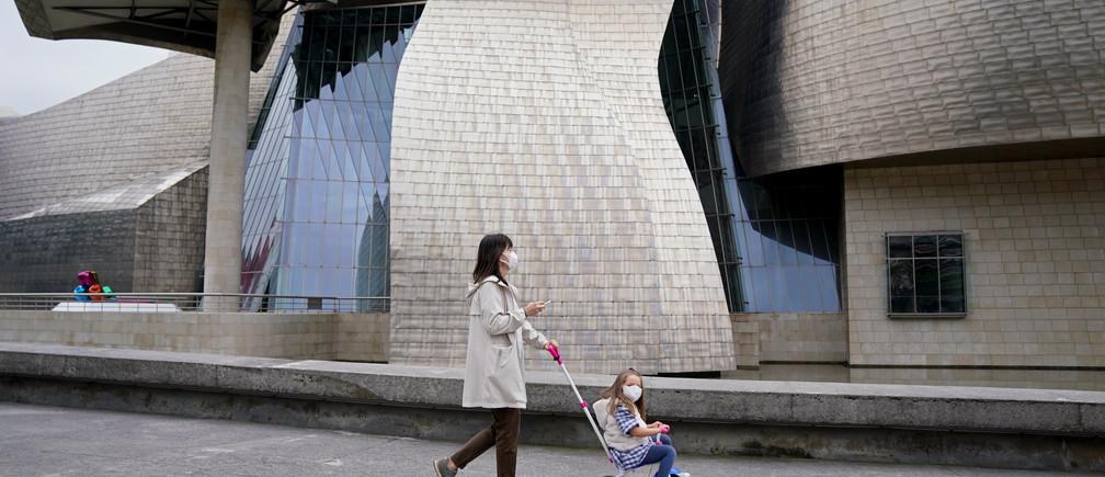 Una madre y su hijo pasan por el Museo Guggenheim, después de que se levantaran parcialmente las restricciones para los niños por primera vez en seis semanas, durante el brote de la enfermedad coronavirus (COVID-19) en Bilbao, España, el 26 de abril de 2020.