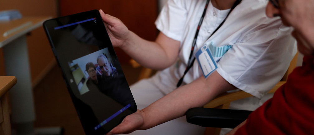 Health worker Emilie Neumann helps a 79 year-old resident to attend an online video call with his relatives at Les Jardins d'Emeraude long-term care unit at Bischwiller departemental hospital, near Strasbourg, during a lockdown imposed to slow the spread of the coronavirus disease (COVID-19), France, April 9, 2020. Picture taken April 9, 2020.   REUTERS/Christian Hartmann - RC2L1G9SF8NP