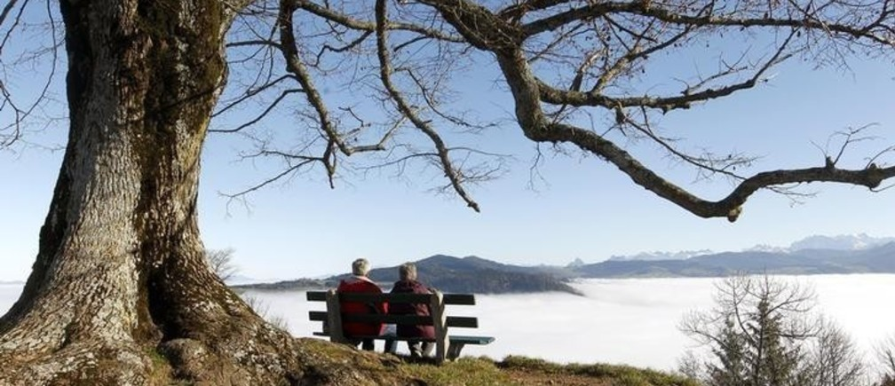 An elderly couple sits on a bench on the peak of Mount Hochwacht (988 metres/3241 ft) as high fog covers the landscape around the Swiss town of Zug November 20, 2012. Reuters/Arnd Wiegmann (SWITZERLAND - Tags: ENVIRONMENT)