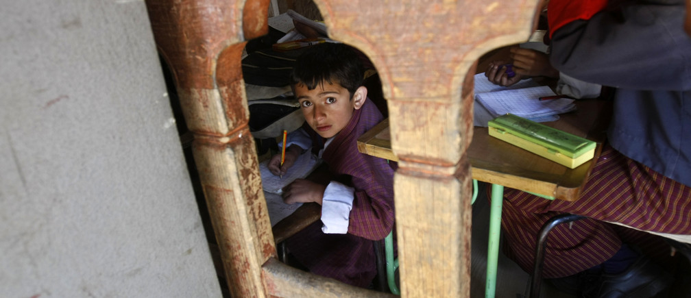 A boy looks out from his classroom at a school in Thimphu, the capital of Bhutan, November 16, 2009. REUTERS/Adnan Abidi (BHUTAN EDUCATION SOCIETY RELIGION IMAGES OF THE DAY) - RTXQSZA