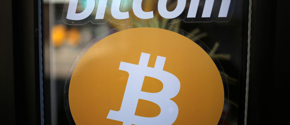 A sign is seen outside a business where a Bitcoin ATM is located in Toronto, Ontario, Canada June 3, 2017.  REUTERS/Chris Helgren - RTX38TW3