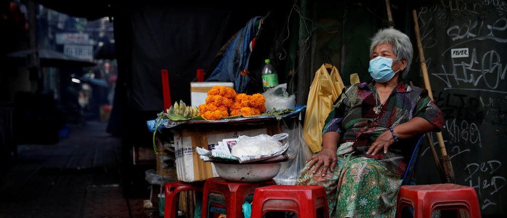 A woman wearing a protective face mask waits for customers, as the spread of the coronavirus disease (COVID-19) continues, in Chinatown, Bangkok, Thailand March 30, 2020. REUTERS/Jorge Silva - RC2BUF9LEK6F