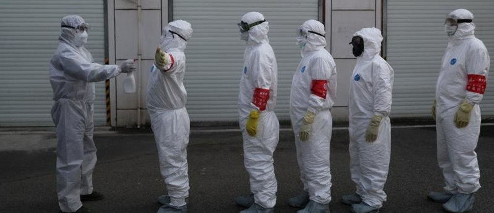 Volunteers in protective suits are being disinfected in a line in Wuhan, the epicentre of the novel coronavirus outbreak, in Hubei province, China February 22, 2020. Picture taken February 22, 2020. China Daily via REUTERS ATTENTION EDITORS - THIS IMAGE WAS PROVIDED BY A THIRD PARTY. CHINA OUT. - RC2U6F9A4U08