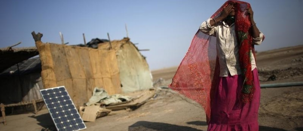 A labourer, who works in a salt pan, covers her face beside a solar panel outside a shelter in Little Rann of Kutch in the western Indian state of Gujarat March 2, 2014. Salt pans begin pumping out sub-soil brine water towards the end of the monsoon in October, and this lasts till end-March, after which it is dried till crystals are formed. The crystals are collected by mid-June and it takes another eight months to process them to make edible salt. India is the third largest producer of salt in the world after the U.S. and China.