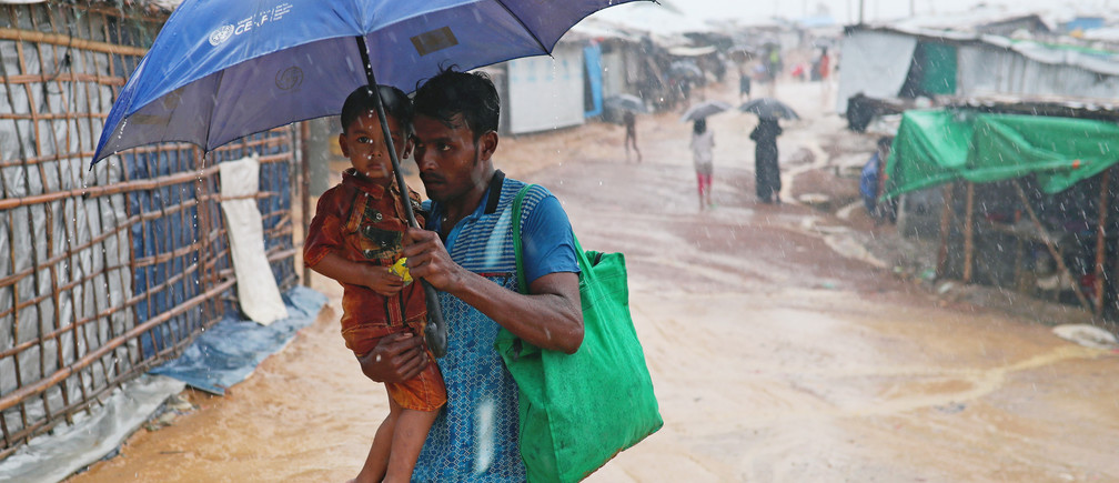 Rohingya refugee man with child returns to his shelter in Kutupalong camp during heavy rain in Cox's Bazar, Bangladesh, July 4, 2018. REUTERS/Mohammad Ponir Hossain - RC1BF34787B0