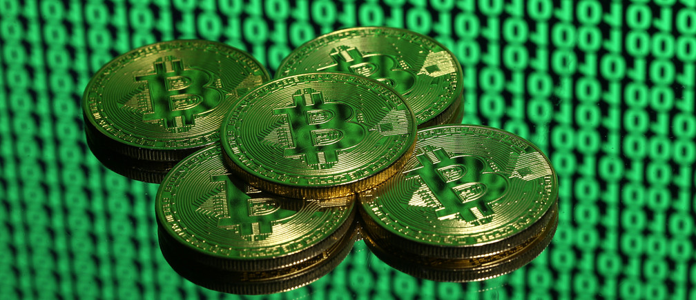 Tokens of the virtual currency Bitcoin are seen placed on a monitor that displays binary digits in this illustration picture, December 8, 2017. Picture taken December 8. REUTERS/Dado Ruvic/Illustration - RC1A57C36840