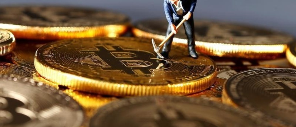 A small toy figure is seen on representations of the Bitcoin virtual currency in this illustration picture, December 26, 2017. REUTERS/Dado Ruvic/Illustration - RC1FC2F47B90