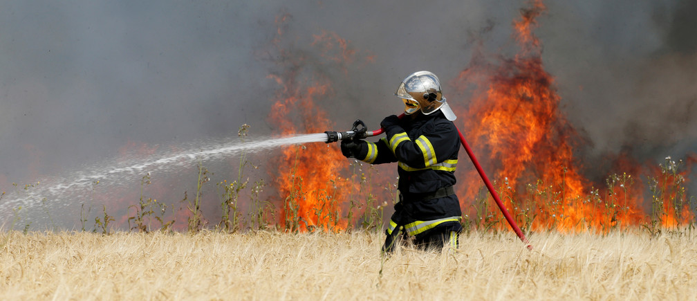 A French fireman sprays water as flames rise in a field of barley during harvest season in Niergnies, France, July 17, 2018.  REUTERS/Pascal Rossignol - RC16495D1AF0
