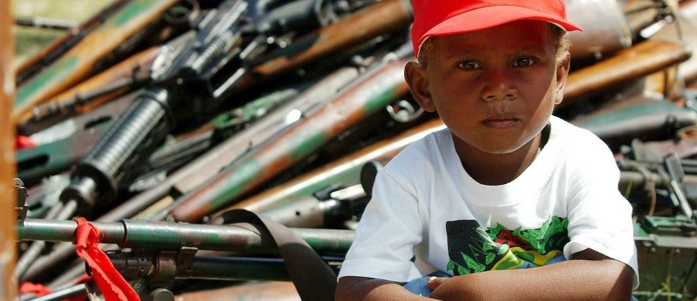 A young boy sits in front of weapons and ammunitions