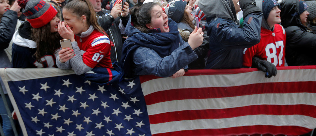 Fans watch the New England Patriots victory parade through the streets of Boston after winning Super Bowl LI, in Boston, Massachusetts, U.S. February 7, 2017.   REUTERS/Brian Snyder - RTX301RG