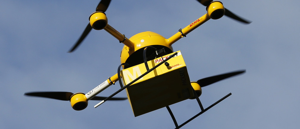 "A prototype ""parcelcopter"" of German postal and logistics group Deutsche Post DHL flies at 100m above ground, its maximum approved height, in Bonn December 9, 2013. DHL on Monday showed its prototype ""parcelcopter,"" which is a modified microdrone that costs 40,000 euros ($54,900) and can carry packages up to 1.2 kg (2.65 pounds). REUTERS/Wolfgang Rattay (GERMANY - Tags: TRANSPORT SCIENCE TECHNOLOGY BUSINESS) - RTX16AXK"