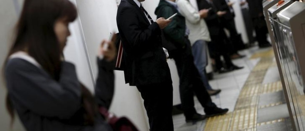 People look at their mobile phones while waiting for a train at a subway station in Tokyo, Japan, October 14, 2015.  Japanese manufacturers' confidence worsened for the second straight month and is expected to fade going forward, a Reuters poll showed, adding to lingering fears of a recession and keeping policymakers under pressure to deploy fresh stimulus. Picture taken October 14, 2015. REUTERS/Yuya Shino