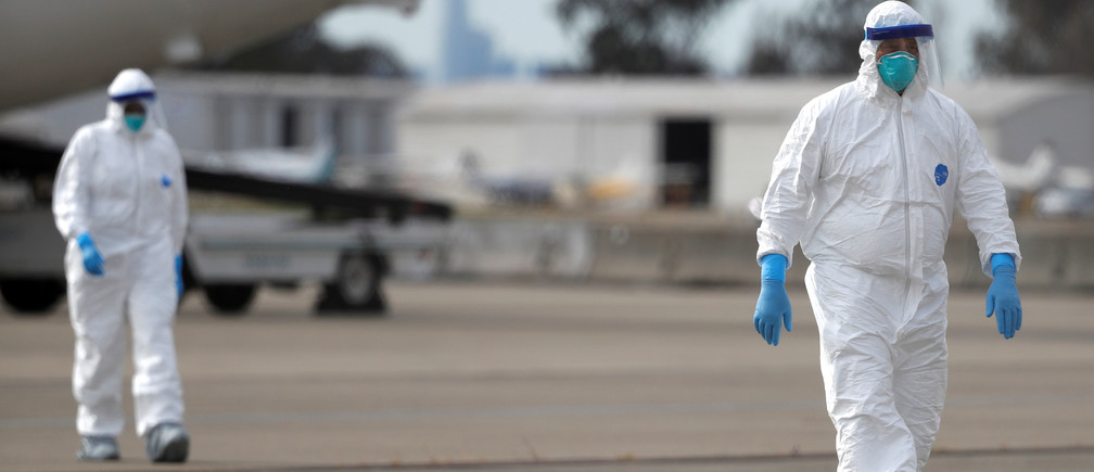 Workers in protective gear walk on the tarmac at Oakland International Airport as authorities continue debarkation from the ship after 21 people on board have tested positive for the COVID-19 coronavirus in Oakland, California, U.S. March 10, 2020. REUTERS/Stephen Lam - RC2BHF92224N