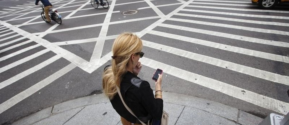 A woman uses her Apple iPhone while waiting to cross 5th Avenue in New York, September 20, 2012.  Apple's iPhone 5 goes on sale tomorrow as Apple works to increase it's market share in the mobile phone market. REUTERS/Lucas Jackson (UNITED STATES - Tags: BUSINESS SCIENCE TECHNOLOGY TELECOMS SOCIETY) - RTR387LK