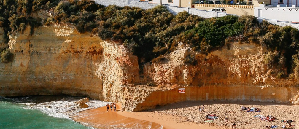 Tourists sunbathing on the beach in Portugal