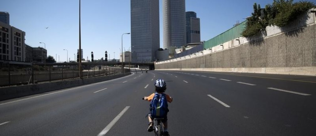 An Israeli boy rides his bike on an empty motorway during Yom Kippur in Tel Aviv, October 4, 2014. Many Israelis take to the streets on bicycles during the holiday of Yom Kippur, or the Day of Atonement, when the country comes to a standstill for 25-hours as observant Jews fast, businesses are closed, and driving is prohibited. REUTERS/Finbarr O'Reilly (ISRAEL - Tags: RELIGION SOCIETY TPX IMAGES OF THE DAY) - GM1EAA41H4601