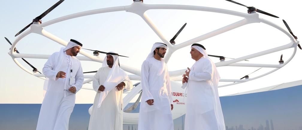 Dubai Crown Prince Sheikh Hamdan bin Mohammed bin Rashid Al Maktoum (2nd R) stands in front of the flying taxi in Dubai, United Arab Emirates September 25, 2017. REUTERS/Satish Kumar - RC11E91B66B0