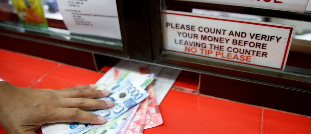 Philippine Peso bills sent by a Filipino working abroad are pictured being received by a relative at a money remittance center in Makati City, Metro Manila, Philippines, September 19, 2018. REUTERS/Eloisa Lopez - RC1AE4678CF0