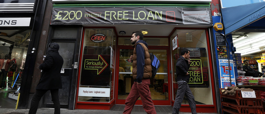 Pedestrians pass by a money-lending shop, supplying payday loans, in north-east London.