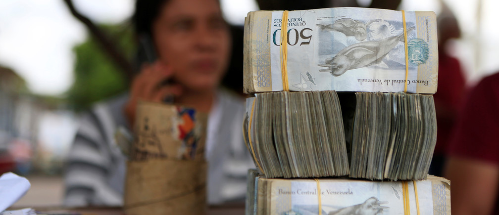 A money changer sits at a table at the border between Colombia and Venezuela, in Paraguachon, Colombia February 16, 2018. Picture taken February 16, 2018. REUTERS/Jaime Saldarriaga