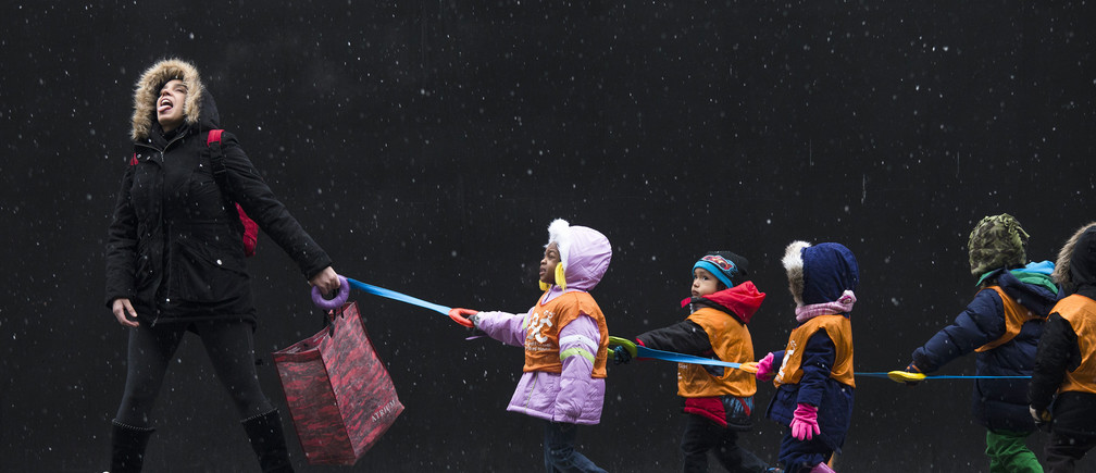 A schoolteacher, who wished to stay unidentified, attempts to catch snowflakes while leading her students to a library from school in the Harlem neighborhood, located in the Manhattan borough of New York on January 10, 2014.  REUTERS/Adrees Latif (UNITED STATES - Tags: ENVIRONMENT EDUCATION TPX IMAGES OF THE DAY) - GM1EA1B00M901
