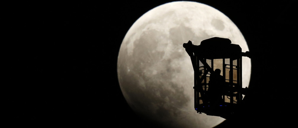"""A man and a woman look at the moon as they ride a Ferris wheel, as a total lunar eclipse begins in Tokyo October 8, 2014. The eclipse is also known as a """"blood moon"""" due to the coppery, reddish color the moon takes as it passes into Earth's shadow. The total eclipse is the second of four over a two-year period that began April 15 and concludes on Sept. 28, 2015. The so-called tetrad is unusual because the full eclipses are visible in all or parts of the United States, according to retired NASA astrophysicist Fred Espenak.   REUTERS/Toru Hanai (JAPAN - Tags: SOCIETY ENVIRONMENT) - RTR49D49"""
